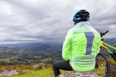 stock image of  a cyclist takes a break to contemplate the landscape