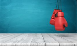 stock image of  3d rendering of two red boxing gloves hanging above a wooden desk in front of a blue blackboard background.