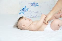 stock image of  dad changing diaper on baby girl on bed, changing nappy, everyday life