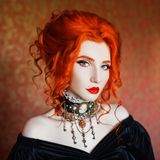 stock image of  dark halloween attire. gothic woman is vampire with pale skin and red hair in a black dress and a necklace on her neck.