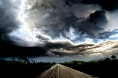 stock image of  dark thunder clouds and dramatic storms over a rural road.