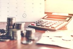 stock image of  debt collection and tax season concept with deadline calendar remind note,coins,banks,calculator on table
