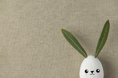 stock image of  decorative white painted easter egg bunny with drawn cute kawaii smiling face. green leaves ears. beige linen fabric background