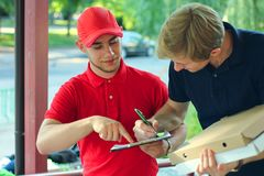 stock image of  delivery man in red asking for a signature