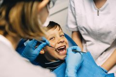 stock image of  dentists with a patient during a dental intervention to boy.