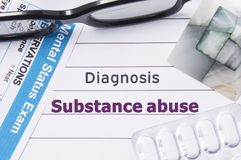stock image of  diagnosis substance abuse. medical notebook labeled diagnosis substance abuse, psychiatric mental questionnaire and pills are on t