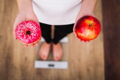 stock image of  diet. woman measuring body weight on weighing scale holding donut and apple. sweets are unhealthy junk food. dieting, healthy eat