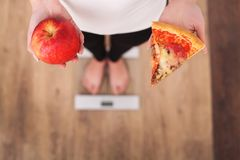 stock image of  diet. woman measuring body weight on weighing scale holding pizza. sweets are unhealthy junk food. dieting, healthy eating, lifest