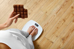 stock image of  diet. woman on weighing scale, chocolate. unhealthy food. weight