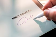 stock image of  digital signature concept with tablet and stylus