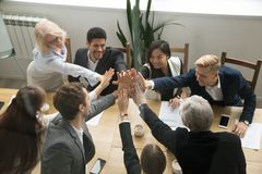 stock image of  diverse business team giving high five showing unity, top view