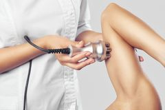 stock image of  the doctor does the rf lifting procedure on the upper arm of a woman in a beauty parlor.