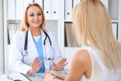 stock image of  doctor and patient discussing something while sitting at the table at hospital. medicine and health care concept