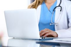 stock image of  doctor typing on laptop computer while sitting at the glass desk in hospital office. physician at work. medicine and