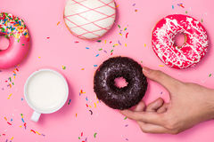 stock image of  donuts, sweetmeats candy on pink background. hand holds donut