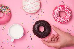 stock image of  donuts, sweetmeats candy on pink background. hand holds donut.
