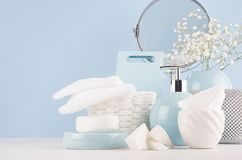 stock image of  dressing table with circle mirror, cosmetic silver accessories and white small flowers in ceramic pastel blue vase on white wood.