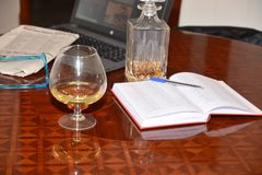 stock image of  drink a glass cognac and bottle alchool work business notebook newspaper glasses hobbies