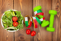 stock image of  dumbells, tape measure and healthy food. fitness and health