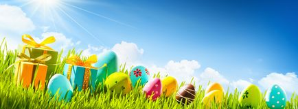 stock image of  easter eggs with green grass and sun