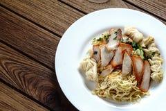 stock image of  egg noodles with red roast pork, dumpling, wontons and veget