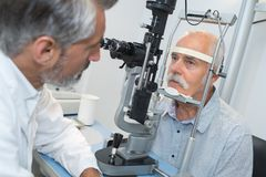 stock image of  elderly man with glaucoma at optician for optical examination