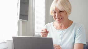 stock image of  elderly senior blond woman working on laptop computer at home. received good news excited and happy