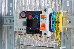 stock image of  in the electrical cabinet circuit breaker, thermostat, terminals.