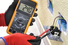 stock image of  electrician technician at work with safety equipment on a residential electrical system