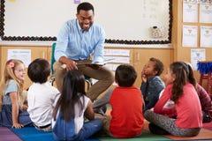 stock image of  elementary school kids sitting around teacher in a classroom