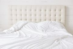 stock image of  empty bed with white soft duvet with nobody. spacious bedroom and comfortable bed for your relaxation and rest. bed time concept.