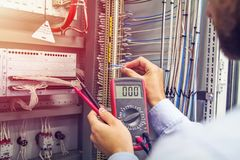 stock image of  engineer tests industrial electrical cabinet. wire in hand of electrician with multimeter. professional in control panel