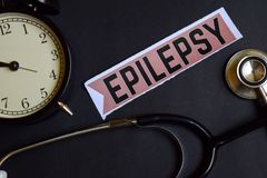 stock image of  epilepsy on the print paper with healthcare concept inspiration. alarm clock, black stethoscope.