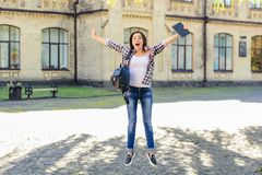 stock image of  exam achievement good luch education college building concept. happy excited jumping female student triumphing and celebrating. ex