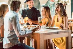 stock image of  experienced chef congratulated by four people at a trendy restaurant