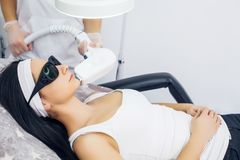 stock image of  face care. facial laser hair removal. beautician giving laser epilation treatment to young woman`s face at beauty clinic. body ca