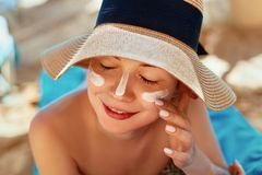 stock image of  facial care. female applying sun cream and smiling. beauty face. portrait of young woman in hat smear moisturizing lotion on skin.