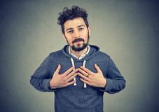 stock image of  faithful man keeps hands on chest near heart, shows kindness expresses sincere emotions