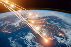 stock image of  falling burning flares of several meteorites of asteroids in the earth`s atmosphere. elements of this image furnished by nasa.