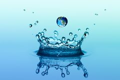 stock image of  water splash in crown shape and falling drop with earth image
