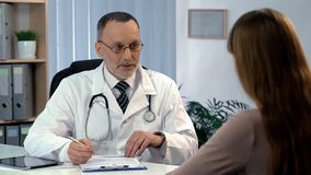 stock image of  family doctor listening to patient, filling out medical insurance, health care