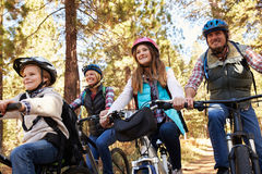 stock image of  family mountain biking in a forest, low angle front view