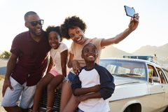 stock image of  family posing for selfie next to car packed for road trip