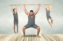 stock image of  family of strongman. father and two sons in vintage costumes drag the rope. family look.