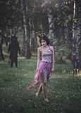 stock image of  a fantastic love story. girl mystical fairy creature fawn in shabby clothes walking in the woods.