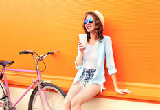 stock image of  fashion pretty woman drinks coffee of cup near retro vintage pink bicycle over colorful orange