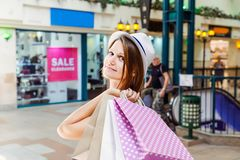 stock image of  fashion young girl portrait. beauty woman with craft paper bags in shopping mall. shopper. sales. shopping center. space for text.
