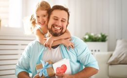 stock image of  father`s day. happy family daughter hugging dad and laughs