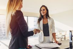 stock image of  female customer shaking hands with real estate agent agreeing to sign a contract standing in new modern studio apartment