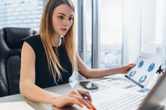 stock image of  female director working in office sitting at desk analyzing business statistics holding diagrams and charts using laptop